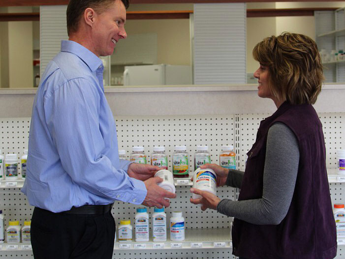 pharmacists helping a customer select vitamins
